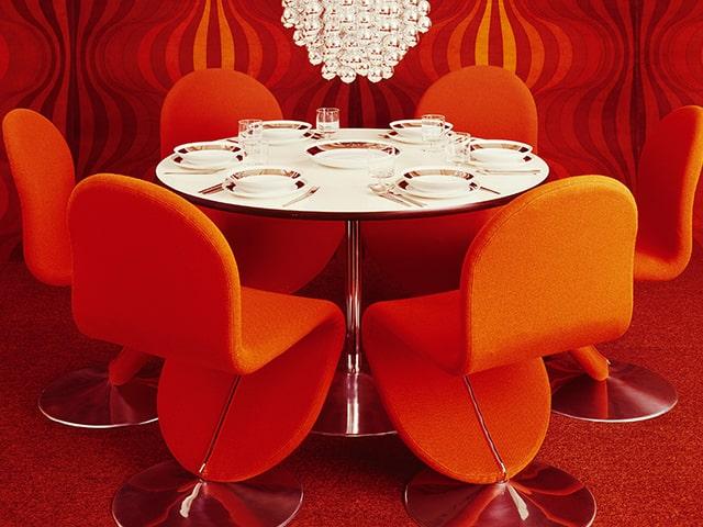 Weisser Tisch mit orangen Stühlen in Zimmer mit orangen Tapeten und orangem Teppich