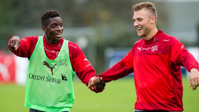 François Moubandje und Silvan Widmer halten sich im Training an der Hand.