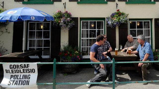 Männer trinken vor einem zum Wahllokal umfunktionierten Pub ein Pint.