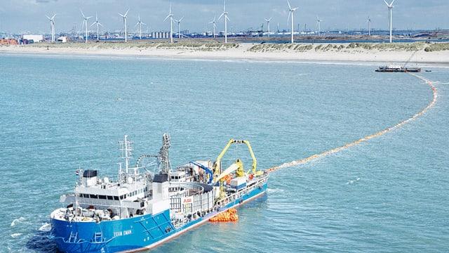 Schiff zieht ein zu verlegendes Hochseekabel hinter sich her, im Hintergrund eine Küste mit Windrädern zur Stromproduktion