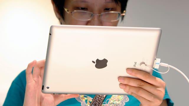 Eine Asiatin hält ein iPad vor sich.