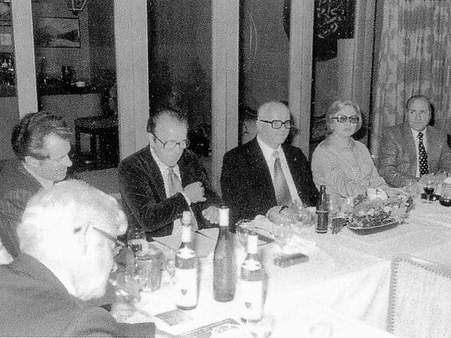 Menschen sitzen an gedecktem Tisch in Restaurant.
