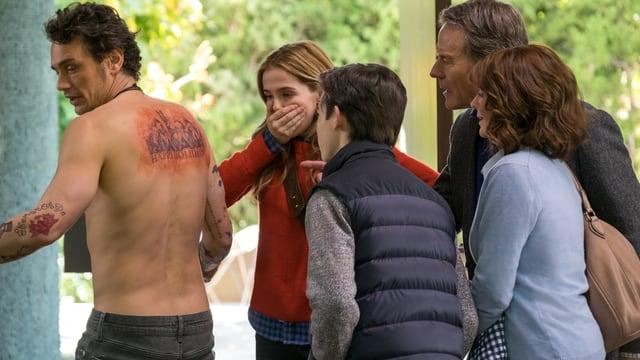 Ein Mann mit einem Tatoo am Rücken. Vier Leute schauen schockiert.