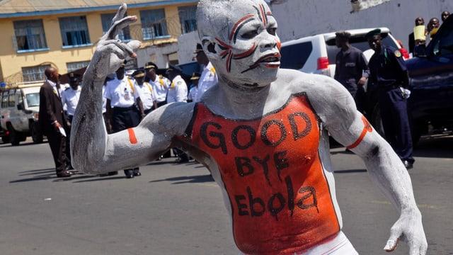 Wess bemalter Mann tanzt mit der Aufschrift «Good Bye Ebola» auf dem Oberkörper.