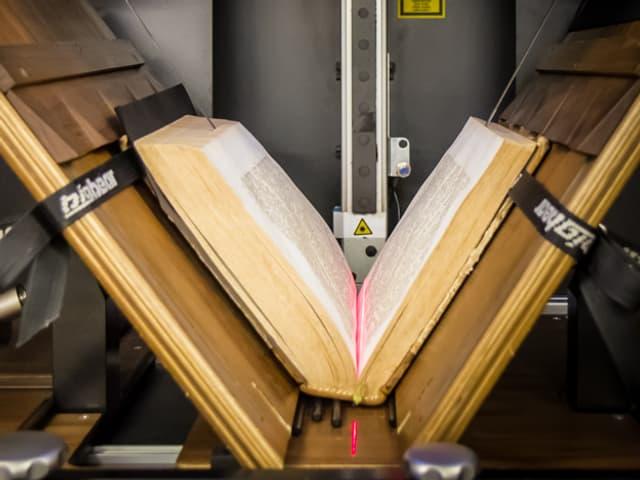Buch liegt halb geöffent in einer Maschine; rote Linie eines Lasers ist im Falz sichtbar.