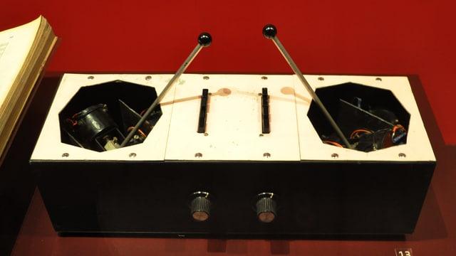 Ein Kasten mit vorne zwei Rundreglern. Oben schaut aus zwei grossen Löchern je ein Steuerungsstab, der sich in alle Richtungen legen lässt.