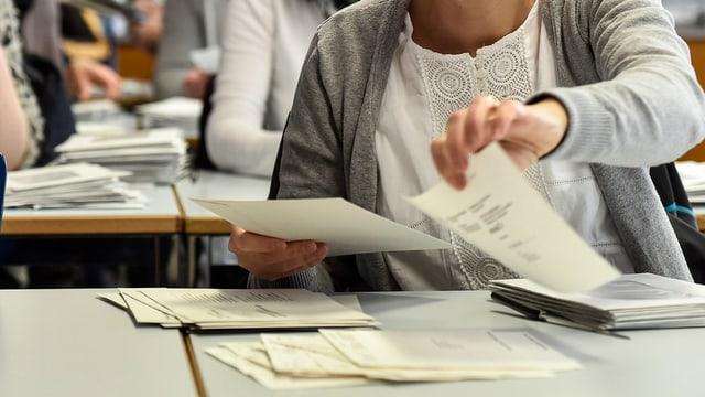 Eine Frau zählt Wahlzettel an einem Urnengang.