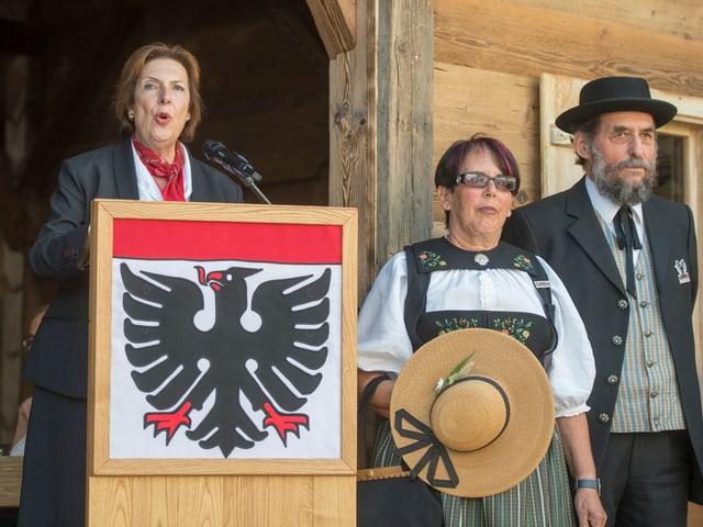 Egerszegi steht an einem Rednerpult, mit der Fahne von Aarau davor. Neben ihr stehen zwei Personen in Trachten.