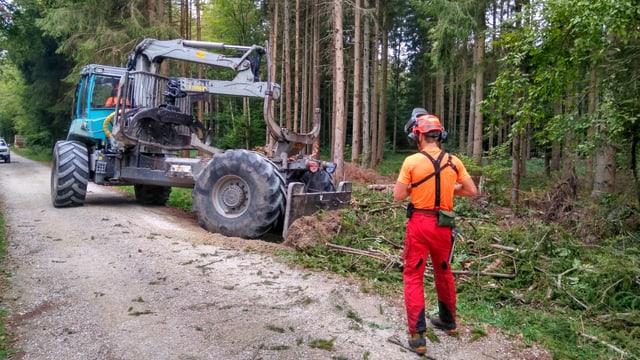 Mann in oranger Kleidung steht vor Bagger im Wald.