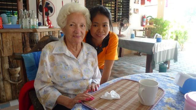 Eine ältere Frau blickt in die Kamera. Neben ihr steht lächelnd eine junge Thai.