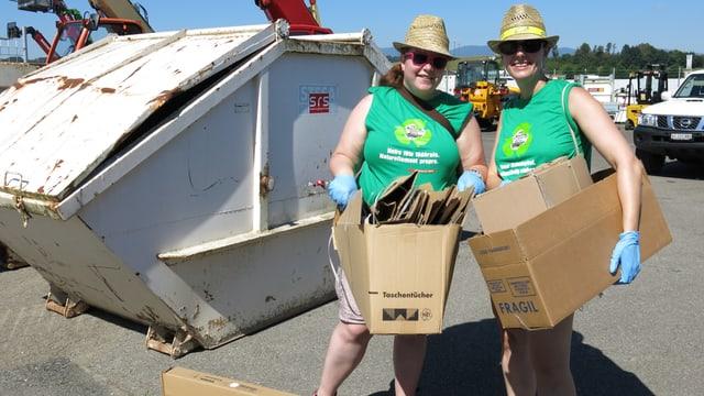 Zwei Frauen tragen Kartons umher.