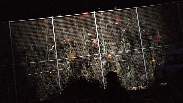 Migranten klettern über den Grenzzaun.