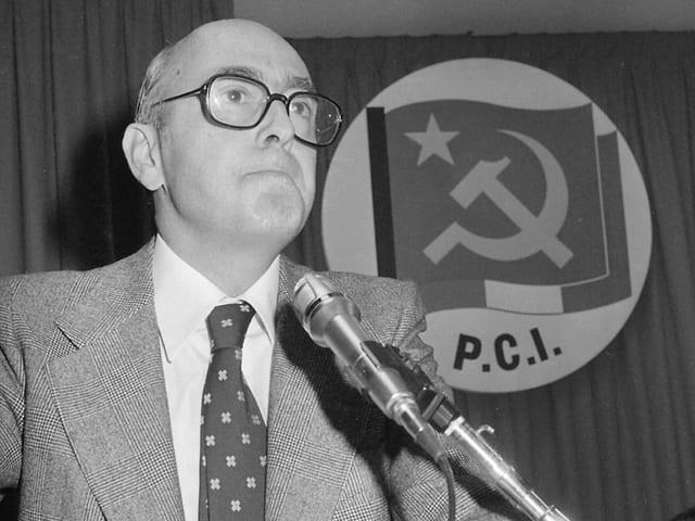 Napolitano an einem Rednerpult, im Hintergrund das Symbol der kommunistischen Partei P.C.I.