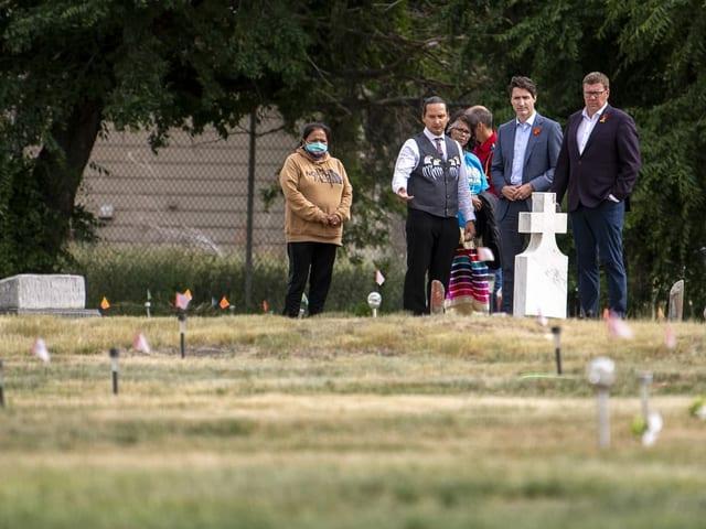 Trudeau und weitere Personen stehen vor einem Friedhof mit Fähnchen und Kreuzen.