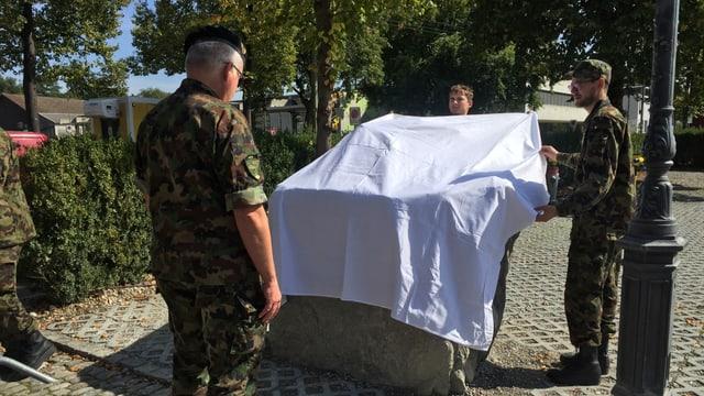 Oberst Thomas Peter vor dem Gedenkstein. Dieser wird mit einem weissen Leintuch bedeckt.