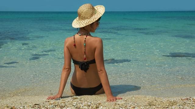Frau im Bikini im Sand sitzend.