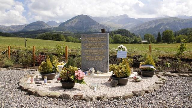 Ein Gedenkstein mit Blumen und Kerzen geschmückt.