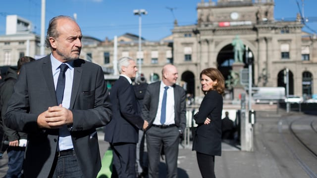 Filippo Leutenegger schaut streng, dahinter bürgerliche Politiker vor dem Hauptbahnhof