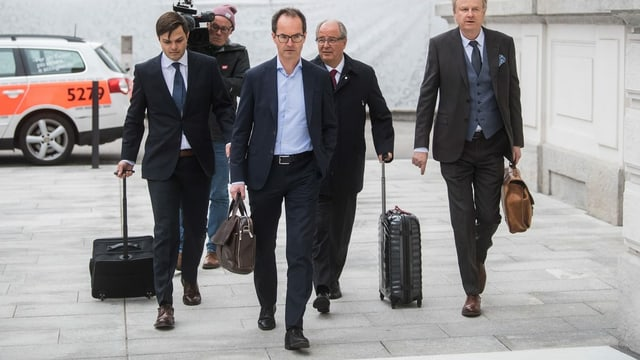 L'anteriur secretari general da la Fifa Urs Linsi (segund da sanestra) cun ses advocats al tribunal penal a Bellinzona.