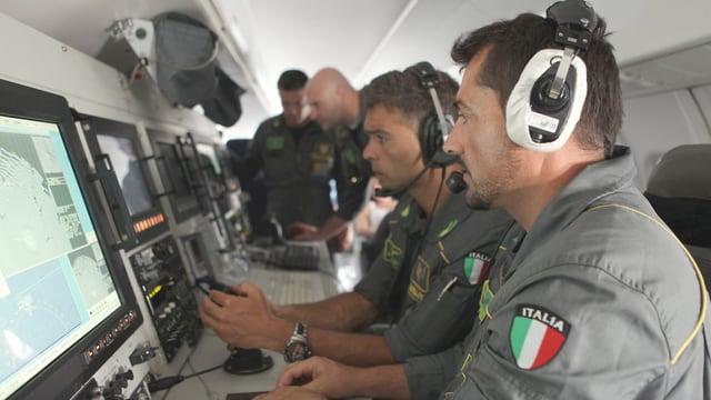 Italienische Polizisten kontrollieren in einem Flugzeug Monitore.