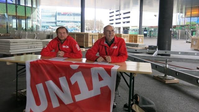 Zwei Gewerkschaftsvertreter sitzen am Tisch auf dem Messeplatz.