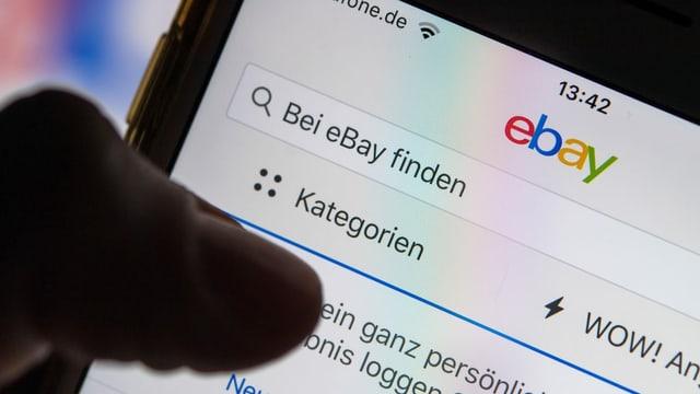 Jemand surft mit dem Handy auf Ebay.
