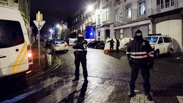 Vermummte Polizisten sperren eine Strasse bei Nacht ab.