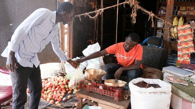 Ein Mann im Flüchtlingslager Dadaab in Kenia kauft Tomaten an einem Stand.