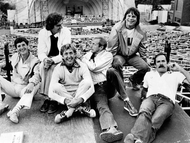 Sechs junge Männer sitzen auf dem Boden. Alle tragen ein weisses Oberteil.