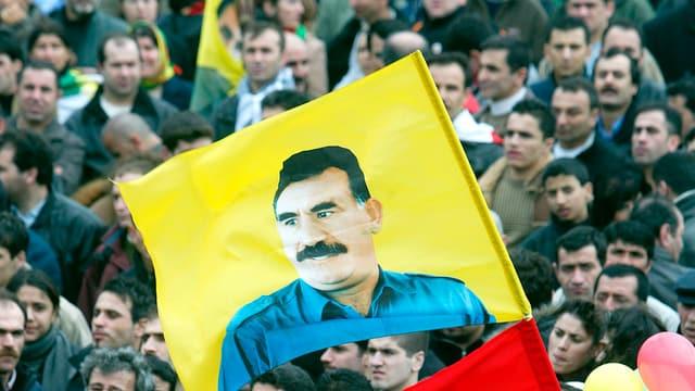 Eine Menschenmenge, darüber weht eine gelbe Fahne mit dem Konterfei Öcalans