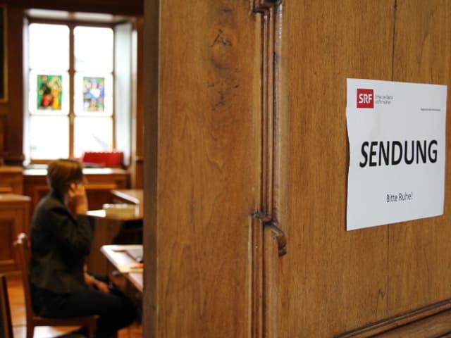 """Blick in den Landratssaal, an der Tür hängt ein Schild """"Sendung""""."""