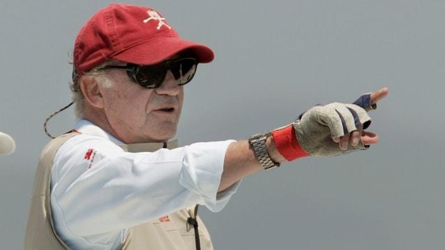 Juan Carlos mit roter Mütze und Sonnenbrille zeigt mit Finger in die Ferne.