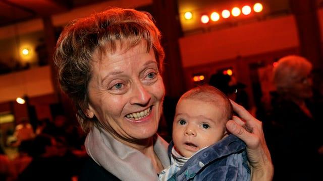 Eveline Widmer-Schlumpf hat Enkelsohn Curdin-Mattia auf dem Arm.