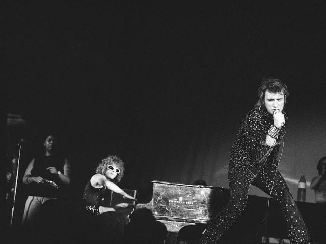 Johnny Hallyday, Mikrofon in der Hand haltend