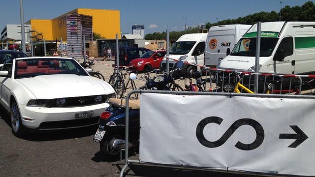 Hinweisschild mit Scope-Logo, daneben ein Cabrio und im Hintergrund ein Logistik-Gebäude des Hafens.