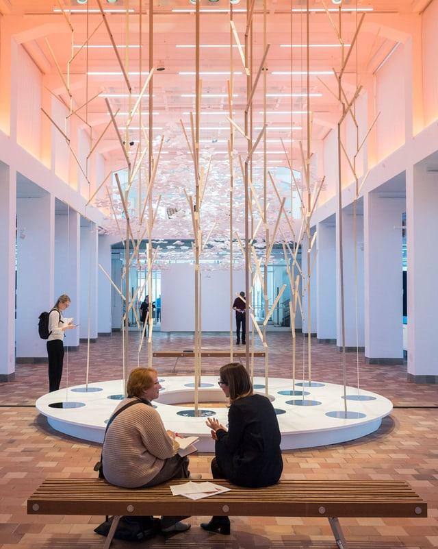 Zwei Museumsbesucherinnen sitzen vor einer Skulptur aus Holzstäben.