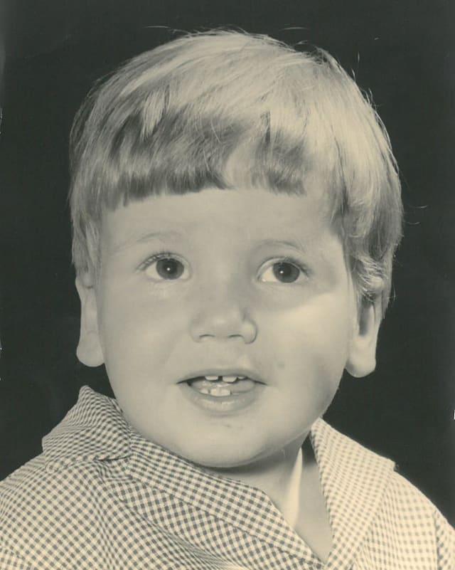 Porträtfoto von einem kleinen jungen mit einem Pagenschnitt und grossen dunklen Augen.