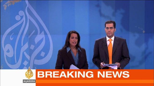 Eine Frau und ein Mann im Nachrichtenstudio davor einen Breaking-News-Einblender.
