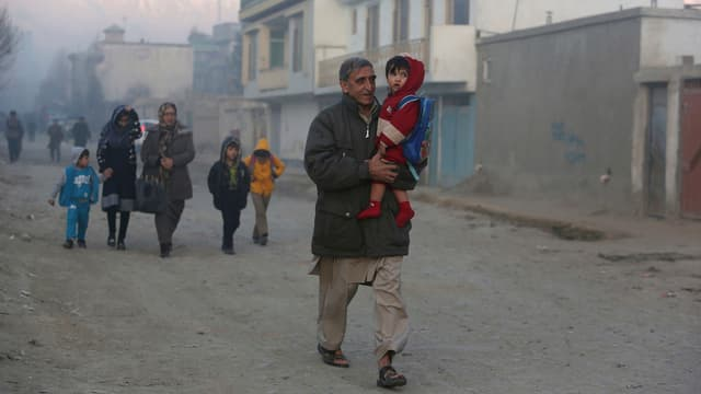 Mann mit Grosskind auf dem Arm läuft durch eine staubige Strasse