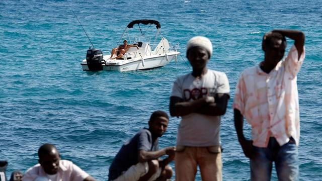 Europäische Wirklichkeit: Während ein Mann auf dem Mittelmeer fischt und die Sonne geniesst, warten gestrandete Flüchtlinge an der Grenze zwischen dem italienischen Ventimiglia und dem französischen Menton.