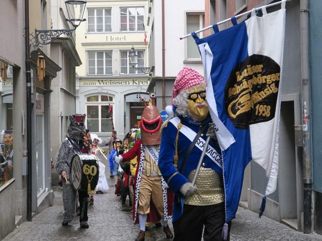 Eine Luzerner Guggenmusig in einer Gasse mit einem Tambourmajor vorne, der eine Fahne hält.