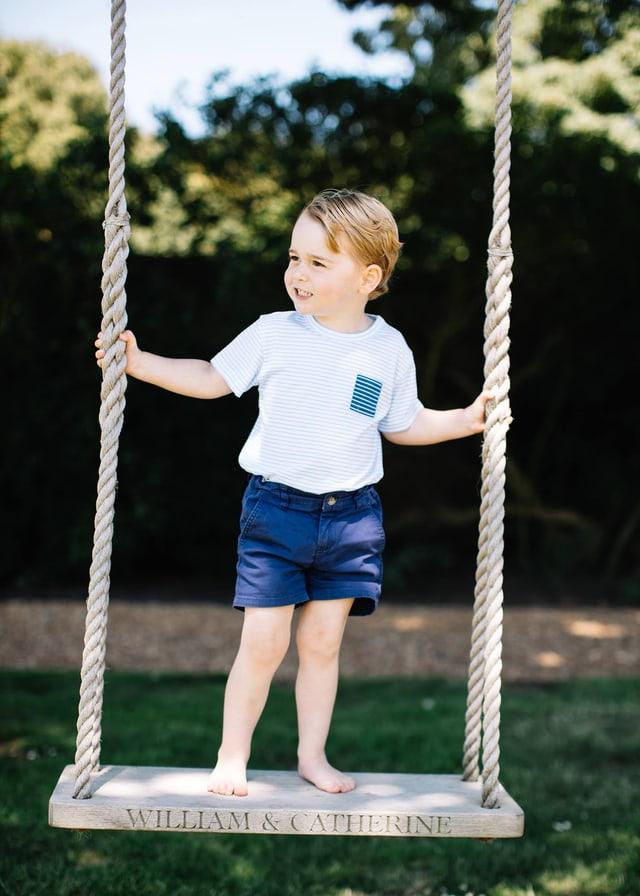 Prinz George steht auf einer Schaukel in einem Garten.