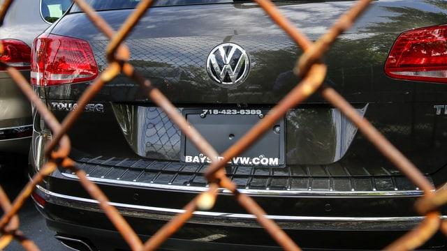 VW-Modell hinter einem rostigen Maschendrahtzaun.