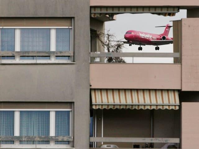 Ein Gebäude, durch einen Abstand sieht man ein Flugzeug.