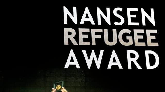 "Projecziun dal scrit ""Nansen Refugee Award"" - fitg pitschen suten dus mauns che tegnan adaut ina medaglia enramada."