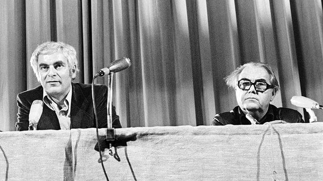 Die Schriststeller Adolf Muschg und Max Frisch auf einer Aufnahme von 1975 an einem Tisch mit Mikrofonen.