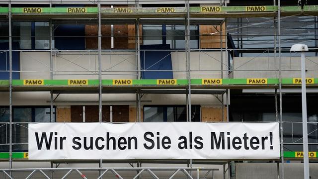 Sicht auf einen Neubau mit Transparent, worauf Mieter angesprochen wird.