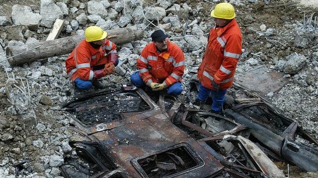 Ausgebranntes Auto unter Betontrümmern