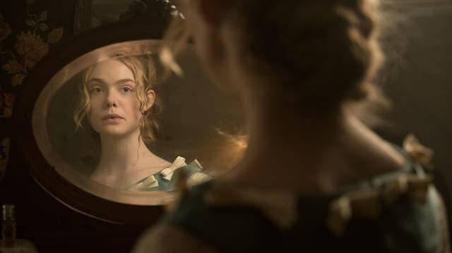Eine junge Frau betrachtet sich im Spiegel.