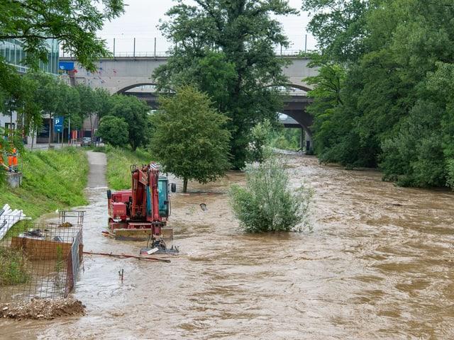 Ein brauner Fluss ist über die Ufer getreten. Im Wasser steht ein Bagger.